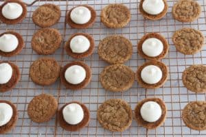 adding buttercream gingerbread cookie sandwiches