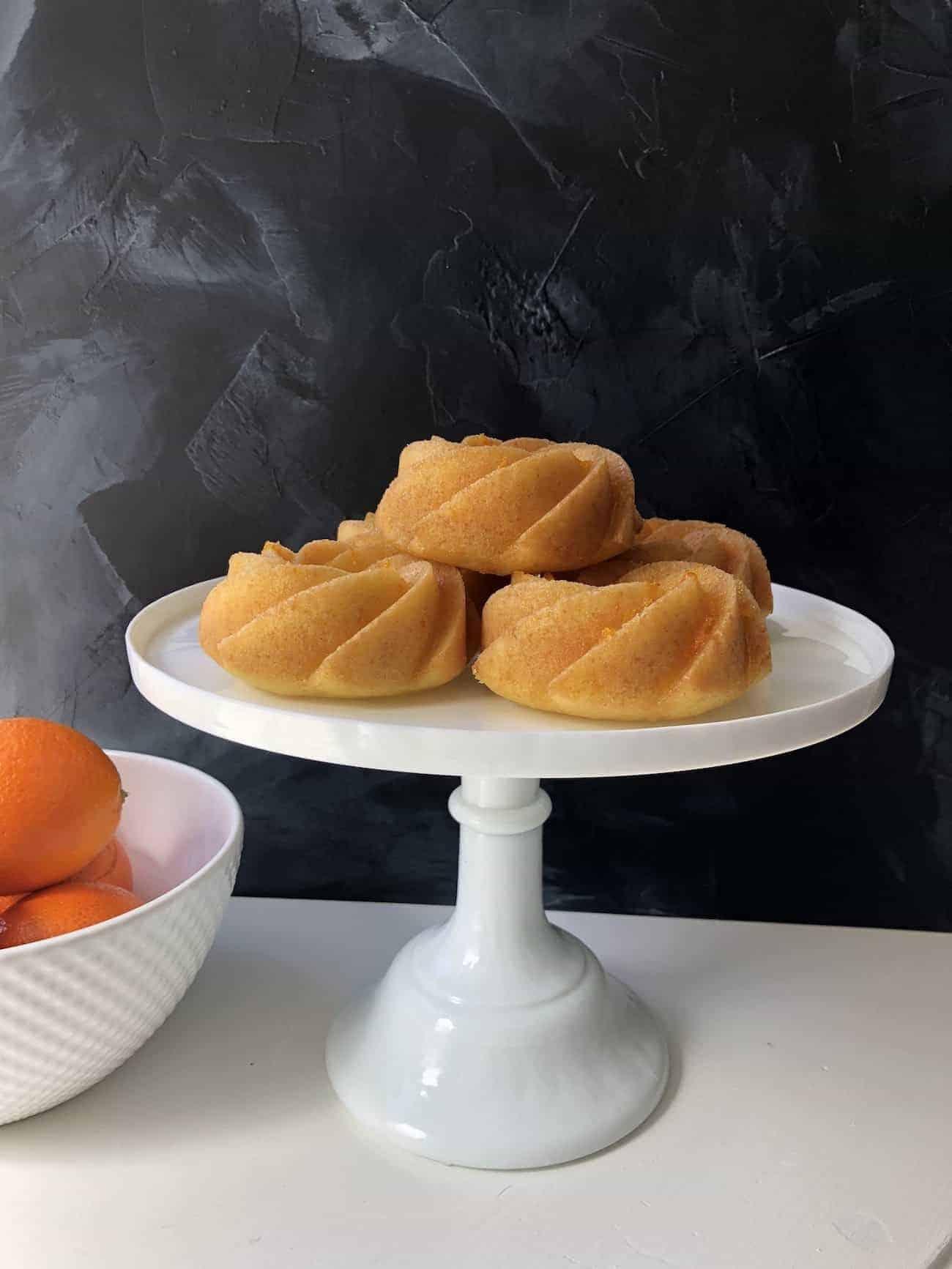 Orange Bundtlette Cakes on Cake Stand with Bowl of Oranges