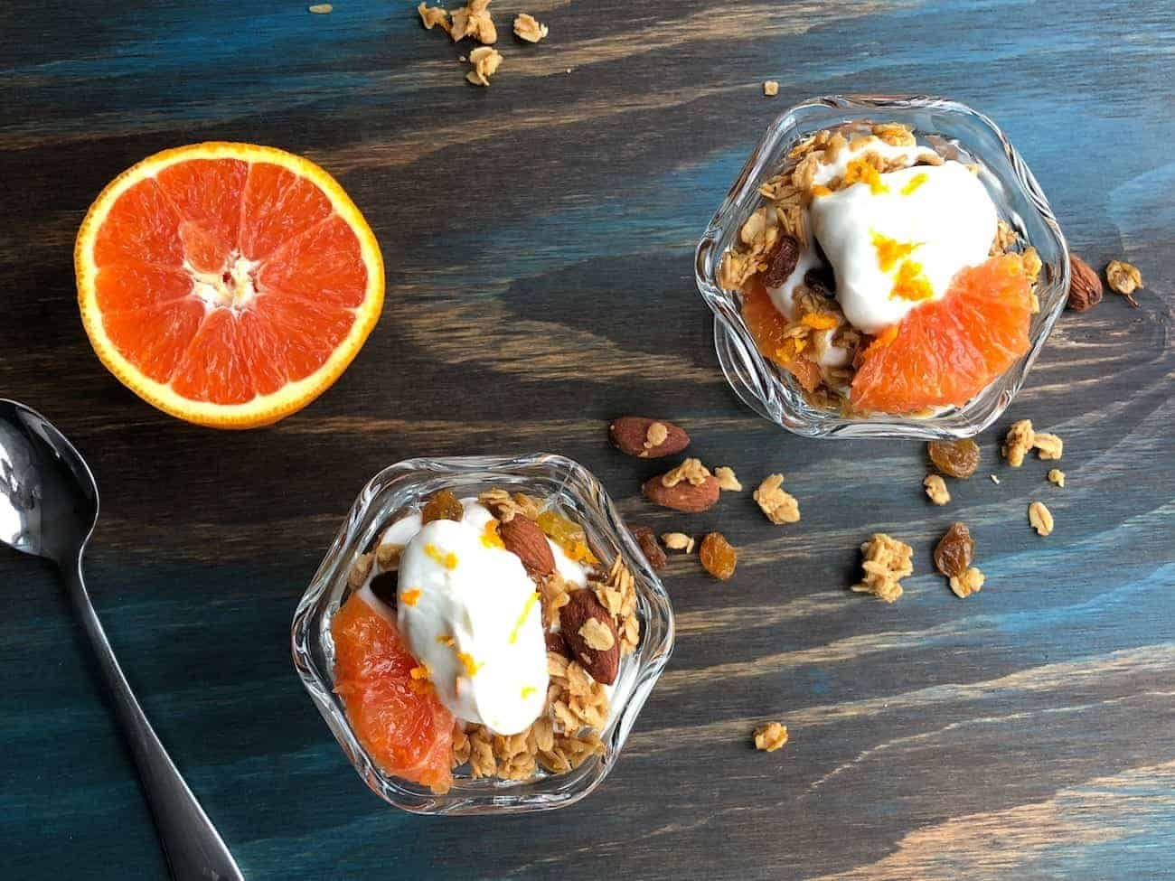 Two Orange and Yogurt Parfaits on a table with half an orange and a spoon
