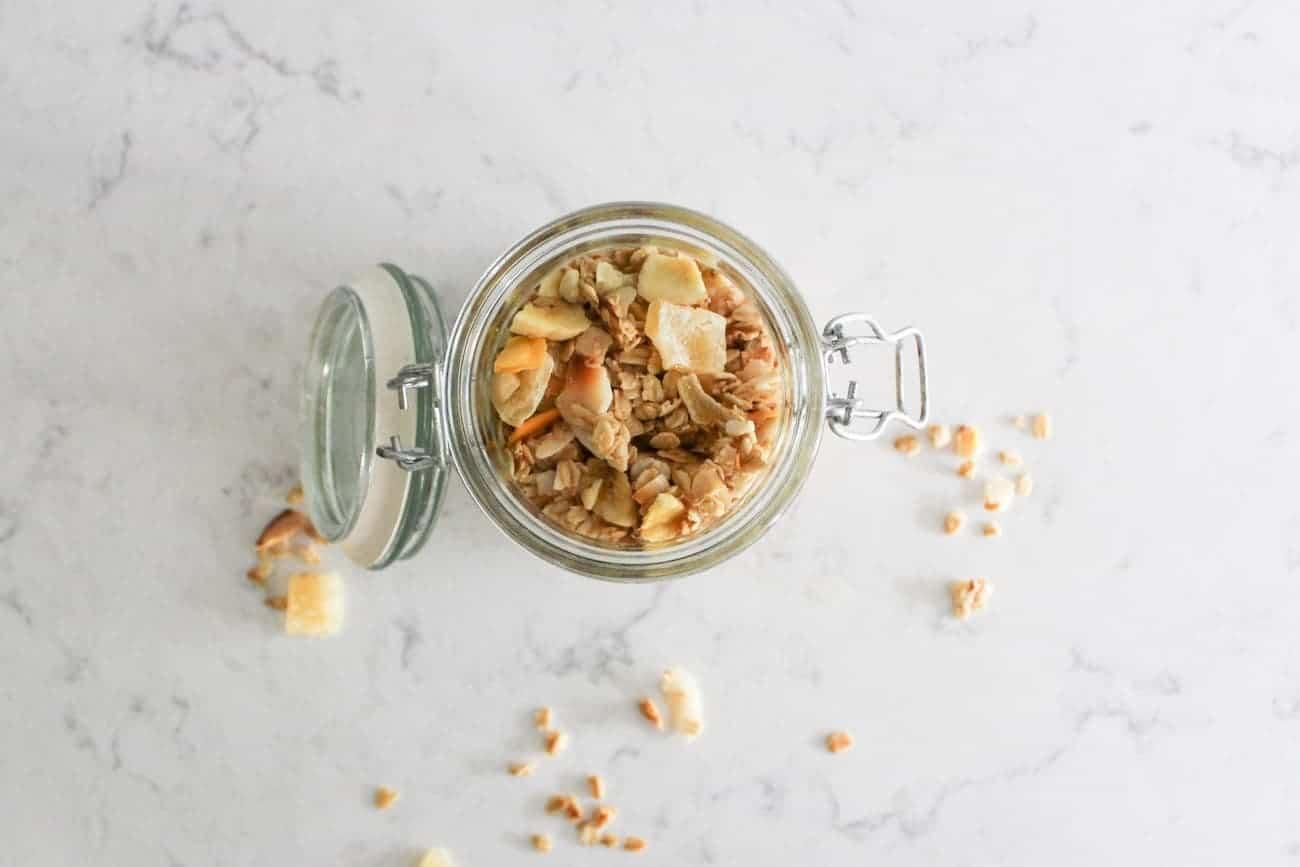 pineapple macadamia nut granola in a jar on marble countertop