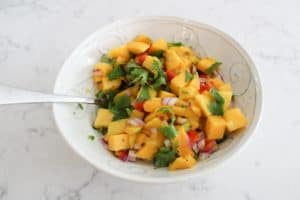 mango salsa in a bowl with a spoon