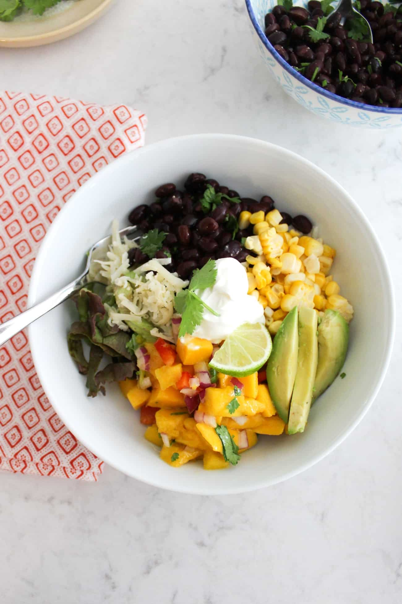 summer burrito bowl with bowl of beans, fork and napkin