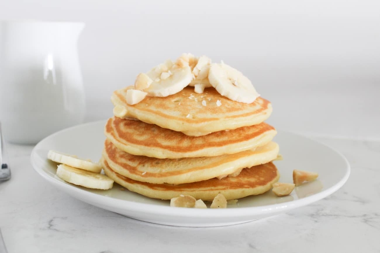 a stack of banana macadamia nut pancakes on a plate with a fork and pitcher of syrup