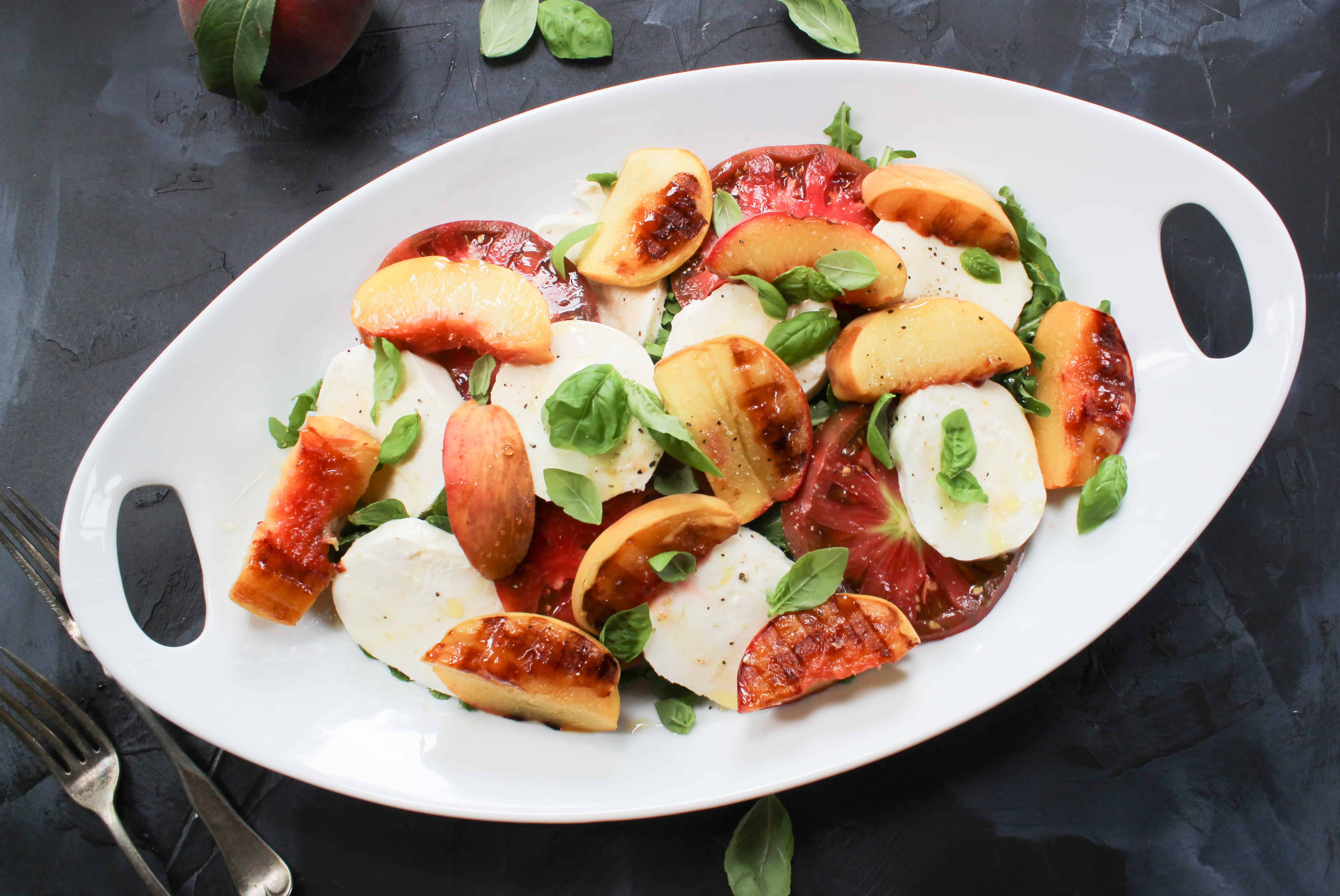 grilled peach caprese salad on slate