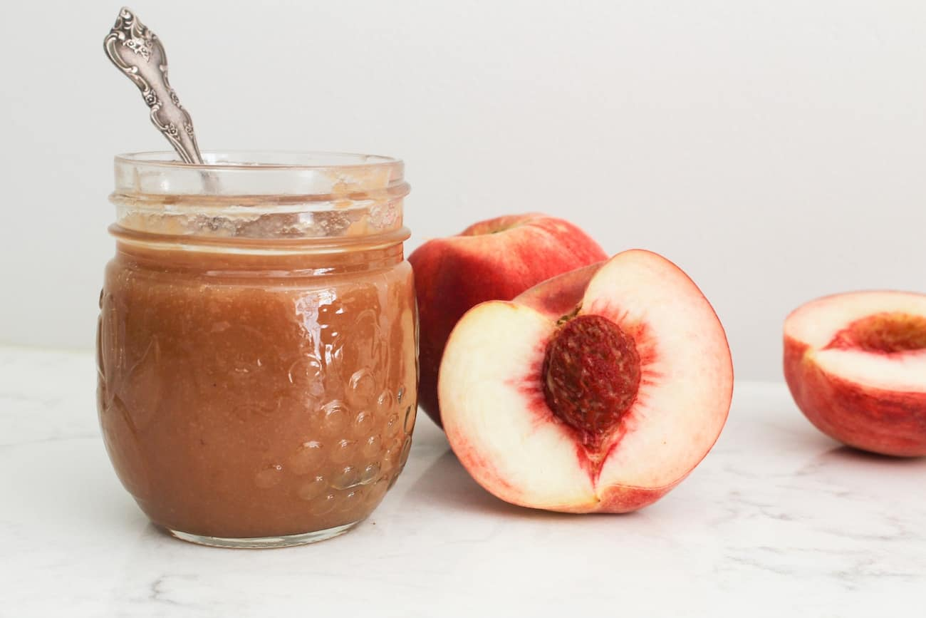 peach butter with spoon and peaches
