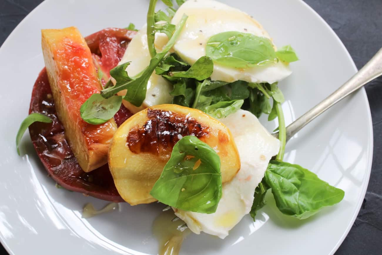 peach caprese salad on white plate with fork