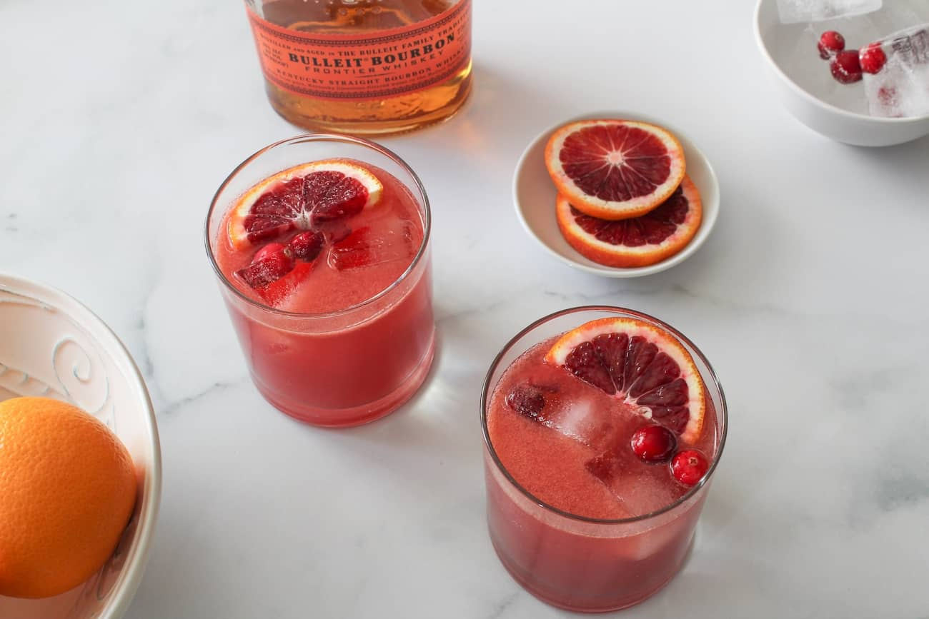blood orange bourbon smash on marble with bowl of oranges