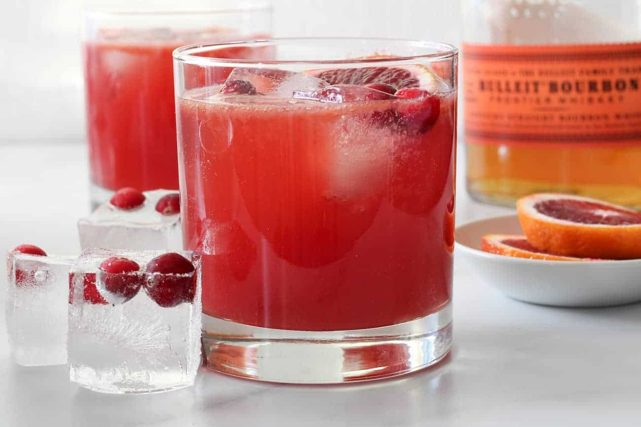blood orange bourbon smash with cranberry ice cubes